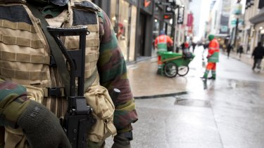 A Belgian Army soldier patrols an otherwise busy shopping street in Brussels on Saturday following the lock down.