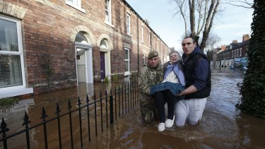 Margaret McCraken, 79, is helped from her home in Carlisle, north-west England.