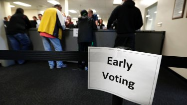 Local residents receive their ballots at the Polk County Election Office on the first day of early voting in Des Moines, Iowa last month.