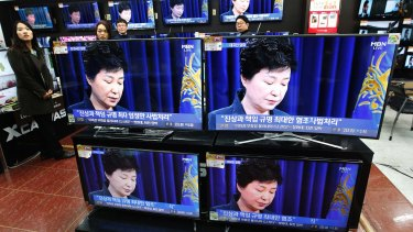 """TV screens show the moment Park Geun-hye took sole blame for a """"heartbreaking"""" scandal that threatens her government."""