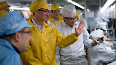 Apple Chief Executive Officer Tim Cook (2nd L) talks to employees as he visits the iPhone production line at the newly built Foxconn Zhengzhou Technology Park, in 2012.