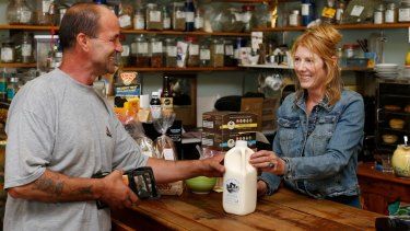 Popular choice: Mick Kir, owner of Upper Gully Organics shop and his shop manager Jenni Duncan with some bottles of Mountain View Organic Dairy Bath Milk, which he sells at his shop.