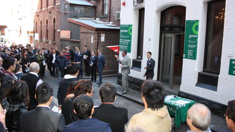 A huge crowd gathers for a Melbourne CBD auction of retail and office premises.