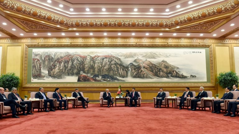 Chinese President Xi Jinping, center right, speaks to Swiss Economy Minister Johann Schneider-Ammann at the signing ceremony for the Articles of Agreement of the Asian Infrastructure Investment Bank at the Great Hall of the People in Beijing on Monday.