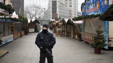 An armed police officer stands guard as the festive stalls remain closed at Berlin Christmas market in Berlin, Germany after a terror attack last year.