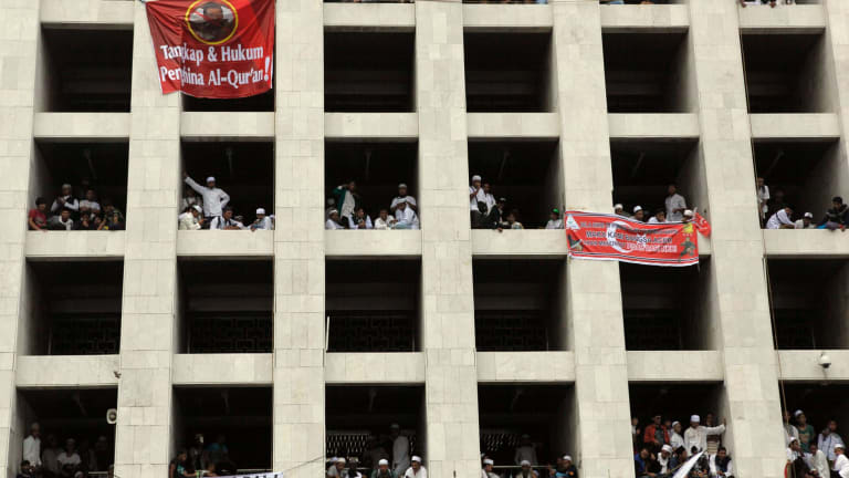 People join the protests from their windows in Jakarta.