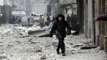 A boy walks on debris at a site hit by what activists said were two barrel bombs dropped by forces loyal to Syrian President Bashar al-Assad in February.