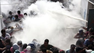 Policemen try to disperse hundreds of migrants by spraying them with fire extinguishers, during a registration procedure at the stadium of Kos, Greece, on Tuesday.