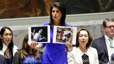 United States' Ambassador to the United Nations, Nikki Haley, holds pictures of Syrian victims.