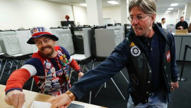John Olsen and Mark Cooper race to be the first to get their ballot in the box on the first day of early voting.