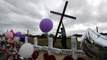 Miguel Zamora stands a cross for the victims of the Sutherland Springs First Baptist Church shooting at a makeshift memorial.