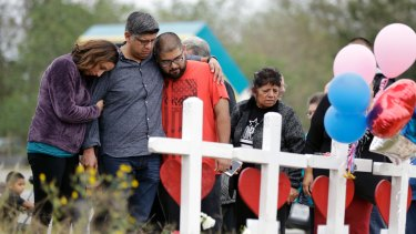 Family and friends gather around a makeshift memorial for the victims of the First Baptist Church shooting.