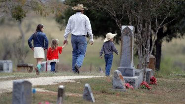 A family arrives for a grave-side service for Richard and Therese Rodriguez at the Sutherland Springs Cemetery.