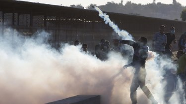 A Palestinian protester throws a tear gas canister away from demonstrators during clashes with Israeli soldiers securing the entrance of the Erez border crossing between the Gaza Strip and Israel on Friday.