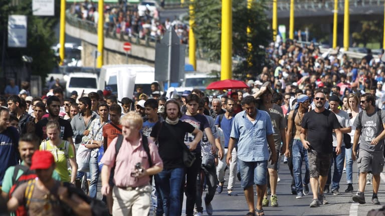 A defiant march to Germany: Migrants walk along the Hegyalja Street in Budapest on Thursday before Hungary set up bus transport to take them.