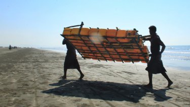 Rohingya fishermen carry a fishing raft made of plastic containers, after their sturdy fishing boats were outlawed.
