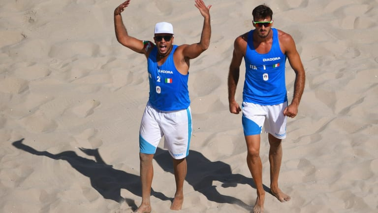 Adrian Carambula,left, and Alex Ranghieri celebrate after defeating Austria in beach volleyball.