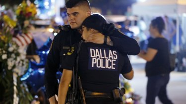 Dallas police officers comfort each other.