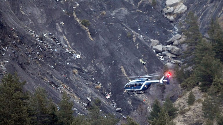 A rescue helicopter flies over debris of the Germanwings passenger jet, scattered on the mountainside, near Seyne-les-Alpes in the French Alps.