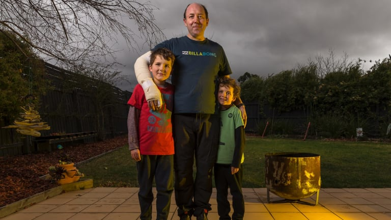 Good to have Dad home: Burns patient Brett Mumford in his Taylors Lakes backyard on Sunday with sons Jarvis, 8, (left) and Casey, 7, and the fire pit (right) that Mr Mumford unwisely poured petrol into.