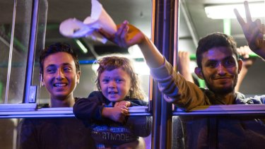 Migrants celebrate after boarding a bus bound for Austria.