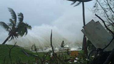 A man running away from high waves caused by Cyclone Pam crashing along the coast in the Vanuatu capital of Port Vila.