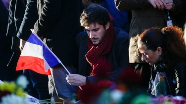 A mourner holds a French national flag as he pays his respects to victims of the terrorist attacks, at Place de la Republique in Paris.