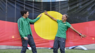 Proud players: Lydia Williams and Kyah Simon with their giant Aboriginal flag in Canada.