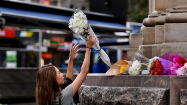 Passers-by lay flowers at the scene of yesterday's Bourke Street Mall tragedy.