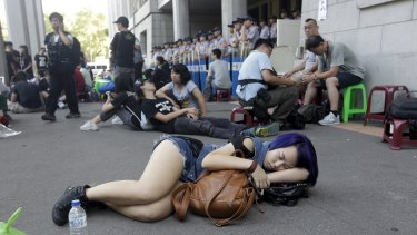A student sleeps on the ground during a protest at the entrance to the Ministry of Education in Taipei on Friday.