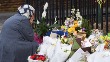 A woman reacts after placing flowers outside Banksia Road Public School in Greenacre.