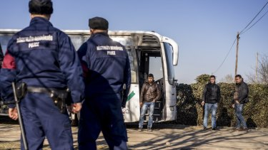 Two Kosovar Albanians and an Afghan man smoke after their bus was stopped by police crossing the border from Serbia, in Assothalom, Hungary.