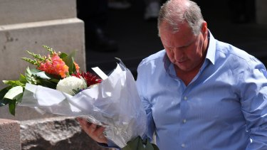 Lord mayor Robert Doyle lays flowers in the Bourke Street Mall.