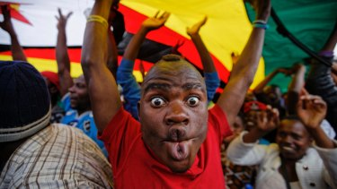 A happy protester stands under a large national flag, at a demonstration of tens of thousands at Zimbabwe Grounds in Harare, Zimbabwe.