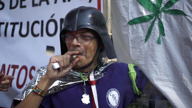 A supporter of the legalisation of marijuana smokes outside the Supreme Court in Mexico City on Wednesday.