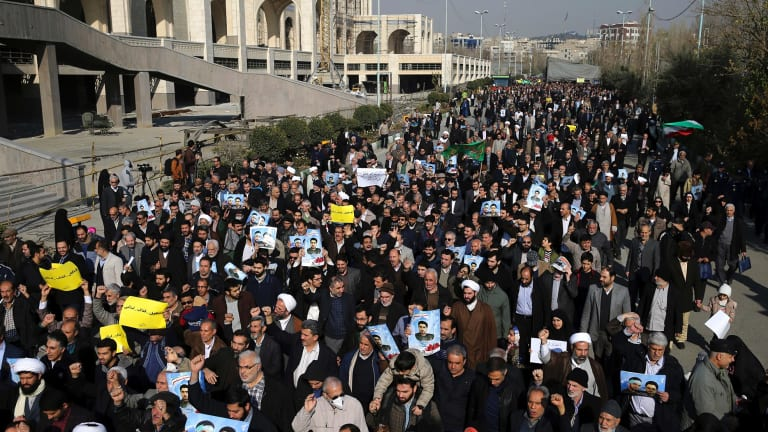 Pro-government demonstrators take to the streets in Tehran on Friday.