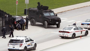 Police officers take cover near Parliament Hill following the shooting incident in Ottawa.