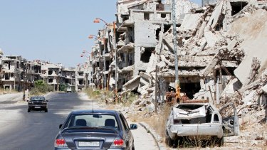 Damaged buildings and rubble line a street in the Syrian city of Homs on Monday.