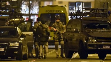 Special operations police take positions during a raid in Brussels on Tuesday where one man was killed. Police say two others are on the run.