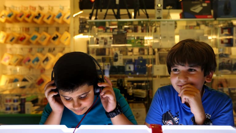 At the shops: Two boys listen to music in a store at Baghdad's Mansour Mall.
