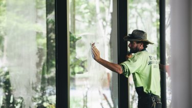Workers clean Indigenous signs from the building's windows.