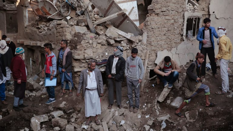 People gather at the site of a Saudi-led airstrike in Saana.