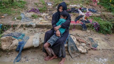 Rohingya woman Mustafa Begum waits for help to transport her sick son Mohammad Riyazullaha to a nearby clinic in Taiy Khali, Bangladesh.