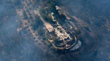 Smoke rises from a home that was destroyed by a fire in the hills east of Napa, California.