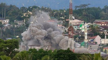 Debris flies in the air near a mosque minaret as Philippine Air Force fighter jets bomb suspected locations of militants in Marawi.