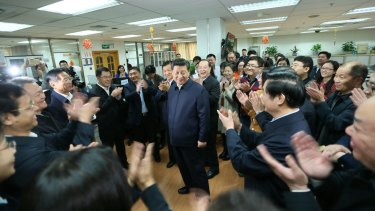 Workers applaud as Chinese President Xi Jinping talks with staff at the People's Daily in February.