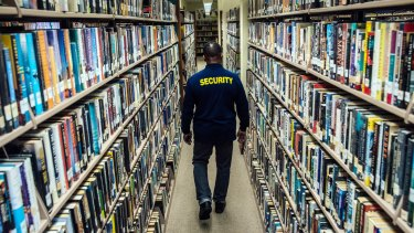 Will Hopper, a security guard, patrols the stacks at the Middletown Thrall Library in Middletown, New York state.