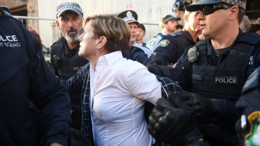 Police escorted Christine Foster past protesters picketing the Liberal fundraising event.