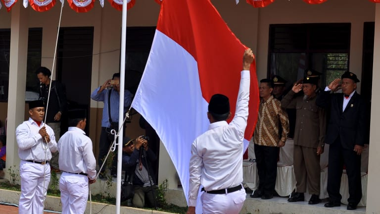 Ali Fauzi salutes the Indonesian flag. Dozens of former terrorist prisoners have been deradicalised in Indonesia.