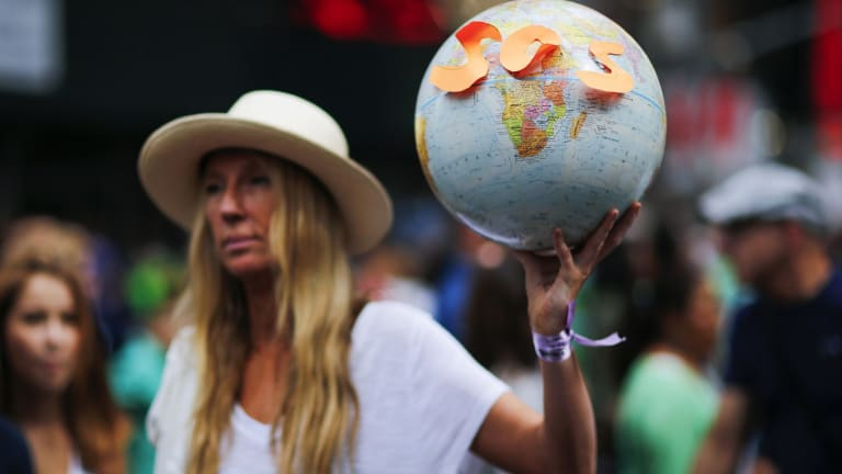 "On the sidelines: A protester takes part in a climate change march in New York earlier this year. The Abbott government is ""looking more and more sad, greedy and isolated"" on the issue of climate change, Greens leader Christine Milne says."
